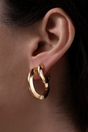Image of model wearing the JENNYBIRD Toni Hinged Hoop Earrings, on model's ear