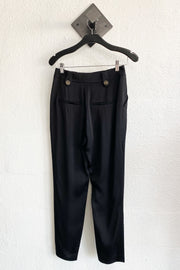Image of the VERONICA BEARD Riana Pant, hanging against white wall, back view