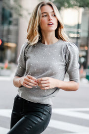 Image of model wearing the AUTUMN CASHMERE Studded Puff Sleeve Crew, standing in street, front view