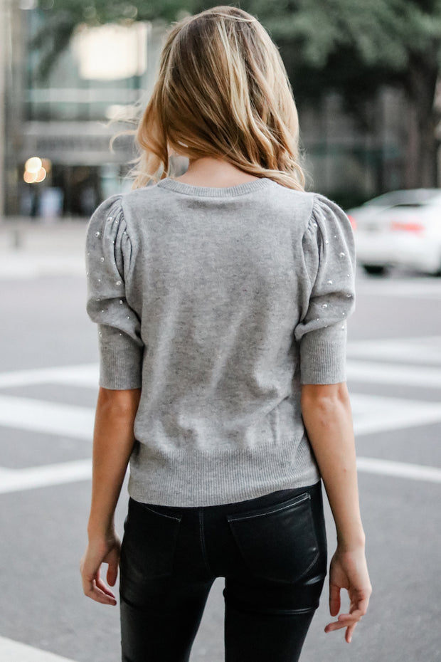Image of model wearing the AUTUMN CASHMERE Studded Puff Sleeve Crew, standing in street, back view