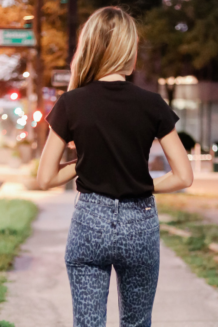 Image of model wearing the AGOLDE Irina Cap Sleeve Bodysuit, standing by street, back view
