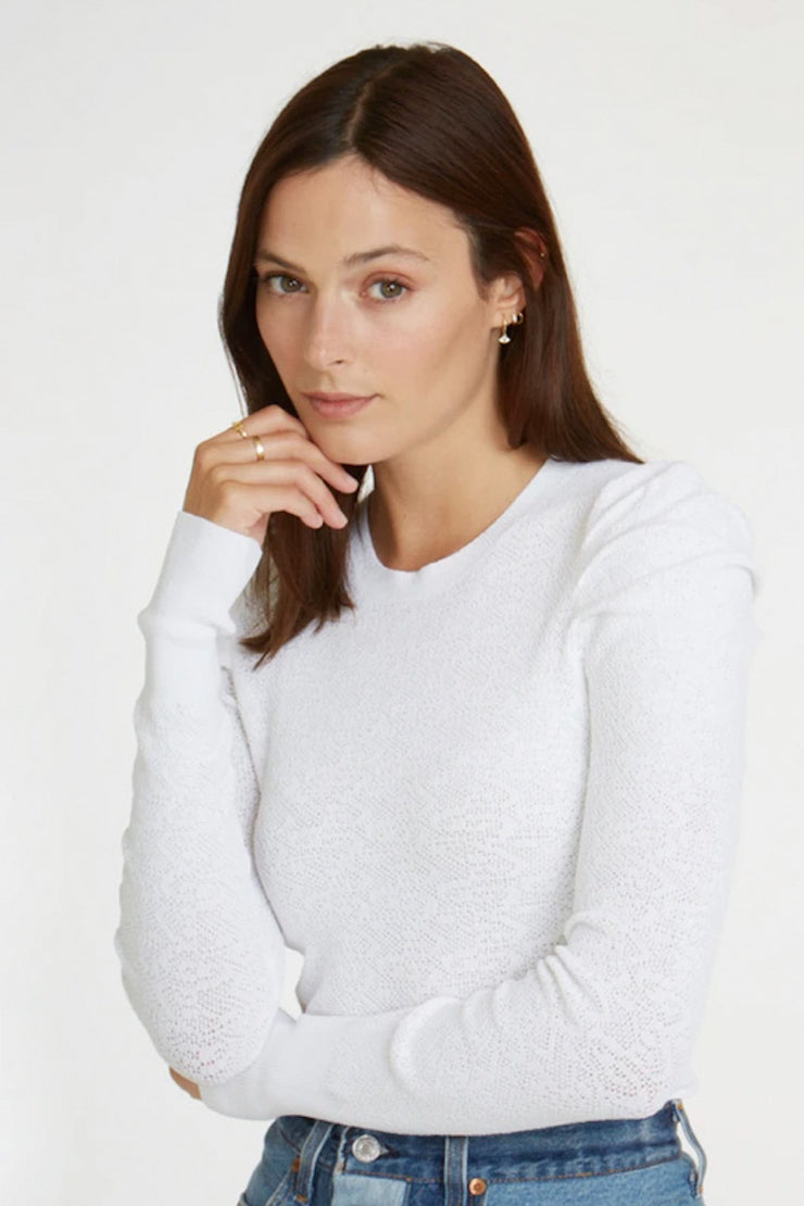 Image of model wearing the AUTUMN CASHMERE L/S Pointelle Puff Sleeve Top, standing infront of white backdrop, front view with arm crossed
