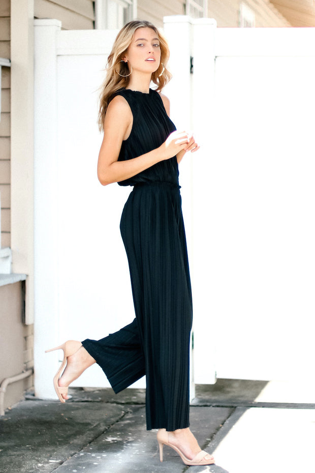 Image of model wearing SUNDAYS Pleated Loose Pant outside, standing infront of white fence - side view