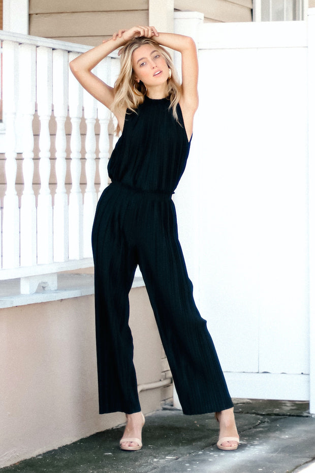 Image of model wearing SUNDAYS Pleated Loose Pant outside, standing infront of white fence - front view with both arms up resting on top of head