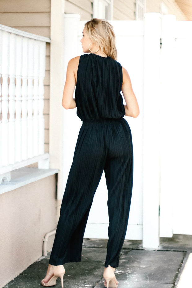 Image of model wearing SUNDAYS Pleated Loose Pant outside, standing infront of white fence - back view