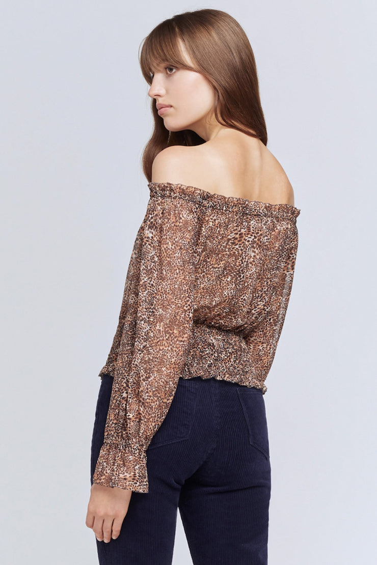 Image of model wearing the L'AGENCE Lilia Top, standing infront of grey backdrop, back view