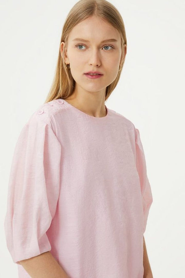 Model wearing the Devin pink top in front of a white background up close side image