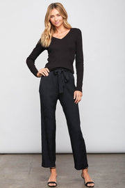 Image of model wearing the SUNDAYS Malone Pant, standing infront of grey backdrop, front view with hand on hip