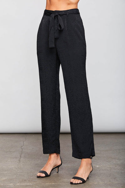 Image of model wearing the SUNDAYS Malone Pant, standing infront of grey backdrop, front view of pant