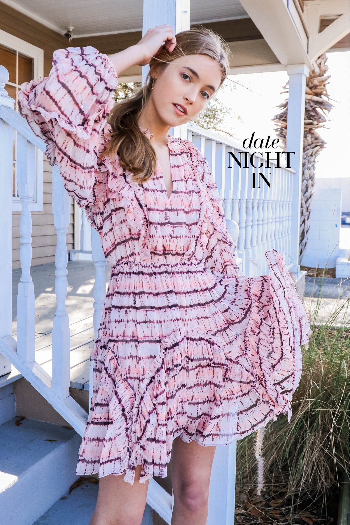 Shop Date Night In - Woman wearing pink knee length dress posing on the porch of a house.