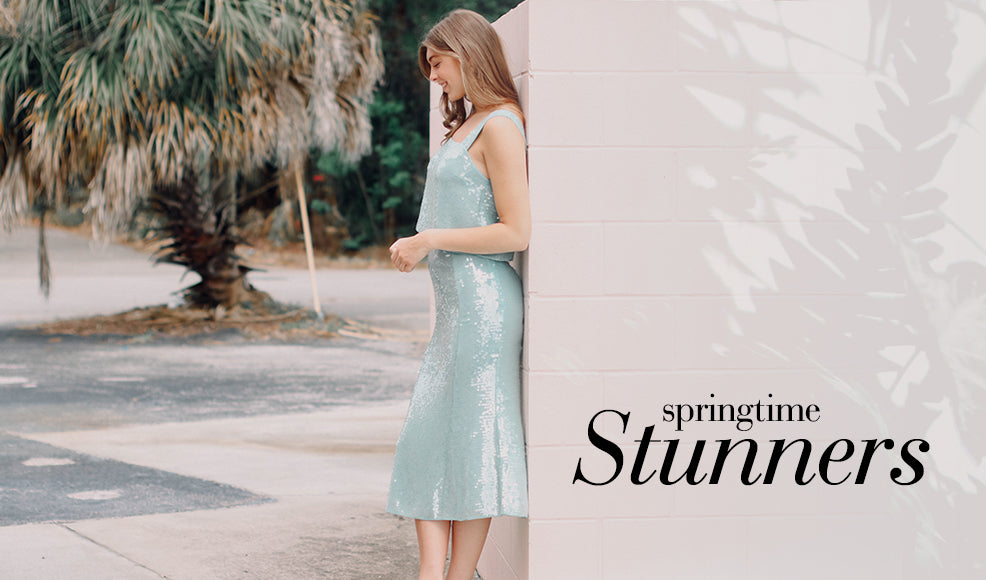 Shop Springtime Stunners - Woman leaning on wall wearing a sparkly 2 piece midi dress.