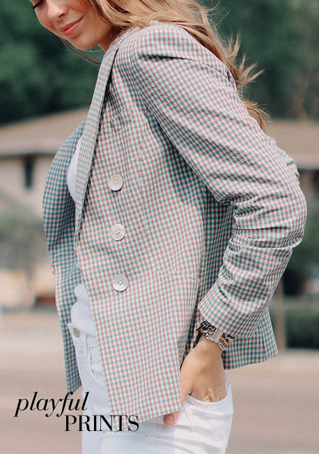 Shop Playful Prints - Woman wearing white and beige plaid blazer with her hands in her back pocket.