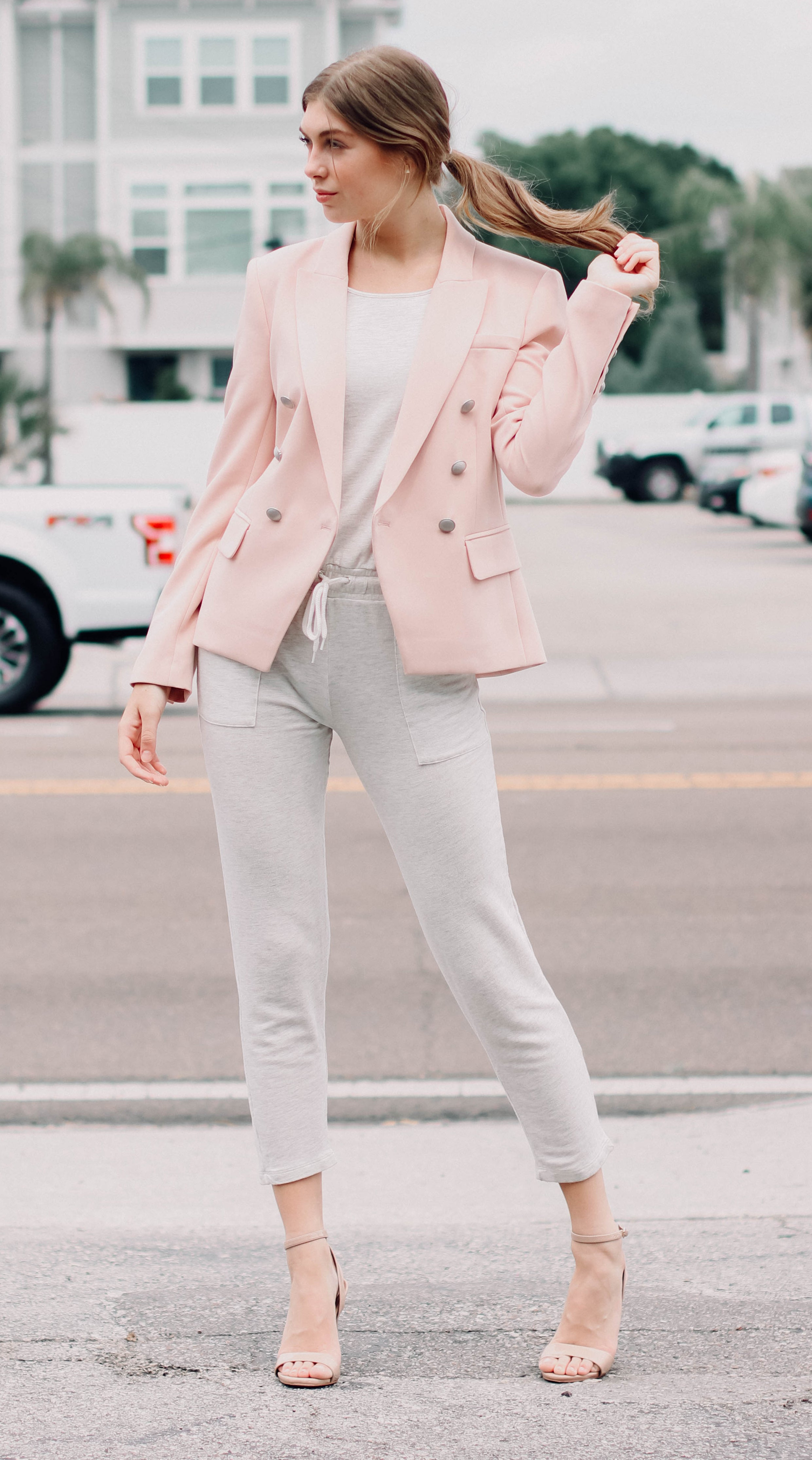 Shop Work From Home Chic - Woman playign with her hair modeling a pink blazer