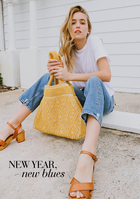 New Year, New Blues - Woman sitting on step in blue jeans and white t-shirt holding a yellow bag.