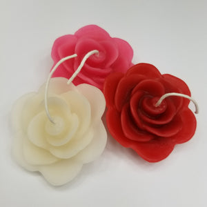 three rose candles, red, white and pink