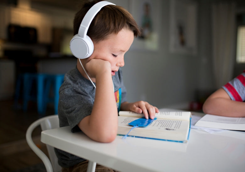 kid listening to music with white headphones on