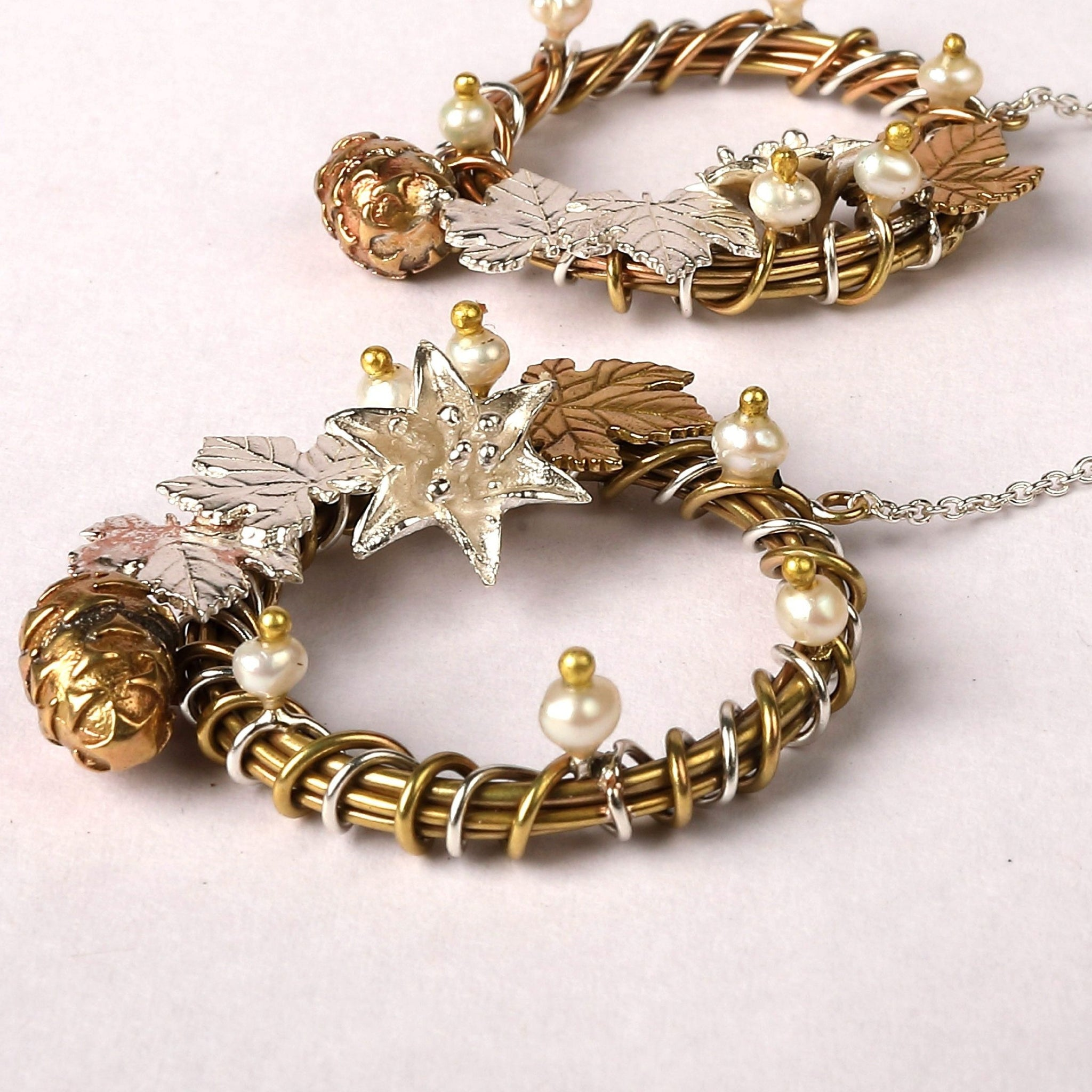 Danglers embellished with silver & brass ivy leaves, brass pine cone, fresh water pearl buds & a silver flower