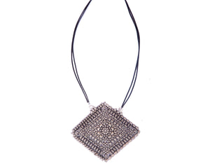 Rhombus shaped pendant strung in twin leather cords