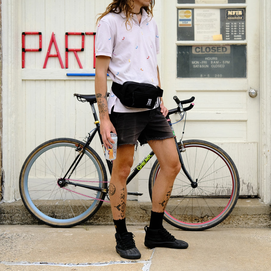 Black fanny pack on male model with bike in background.