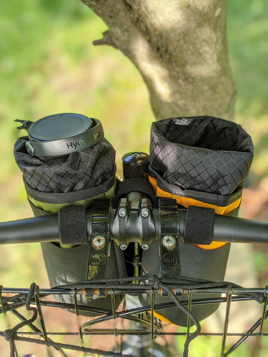 One Mango and One olive snack pack stem bags mounted to handlebars, one open, one with a Hydro Flask®