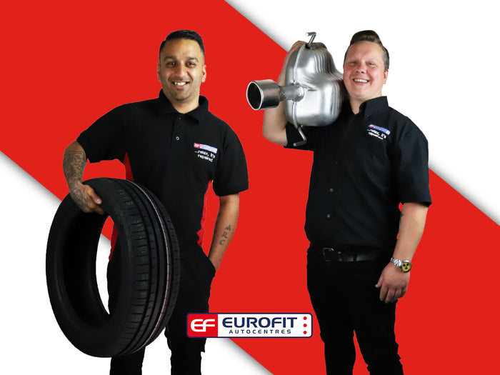Two Eurofit technicians carrying car tyre and engine, with red background