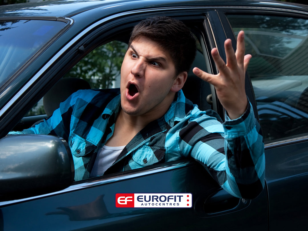 Man in car with arm and head outside of window, shouting at other driver
