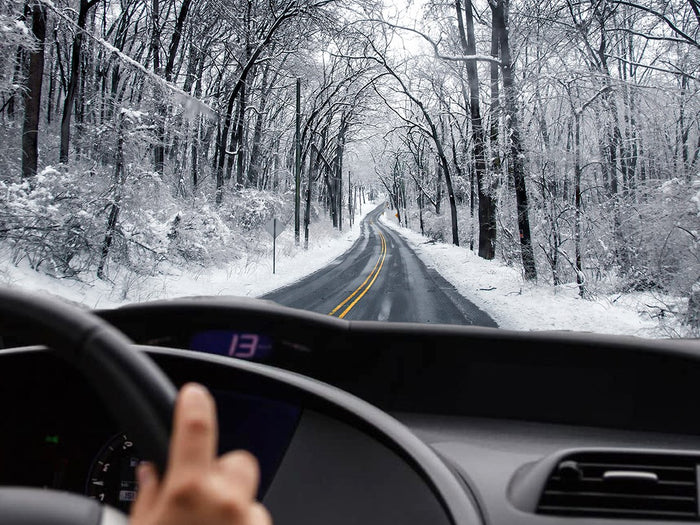 Hands on steering wheel in car driving on Winter road with snow and ice