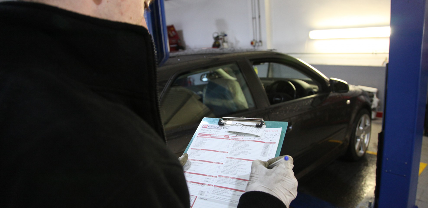 Mechanic back reading checklist and car in background