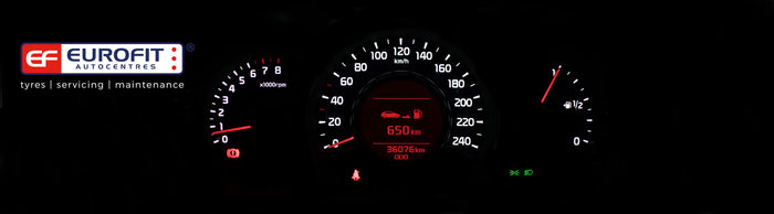Car dashboard speedometer lit up in white and red at night