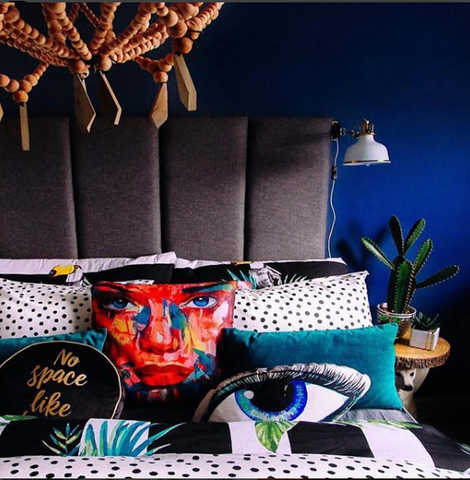 Eclectic Cushions stacked on the bed.