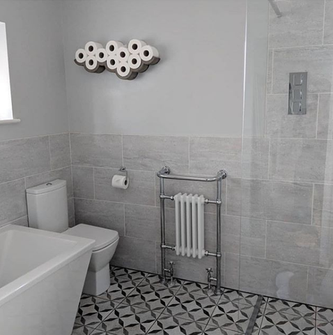 Simple bathroom with sleek grey wall tiles, patterned floor tiles and cloud toilet paper shelf.