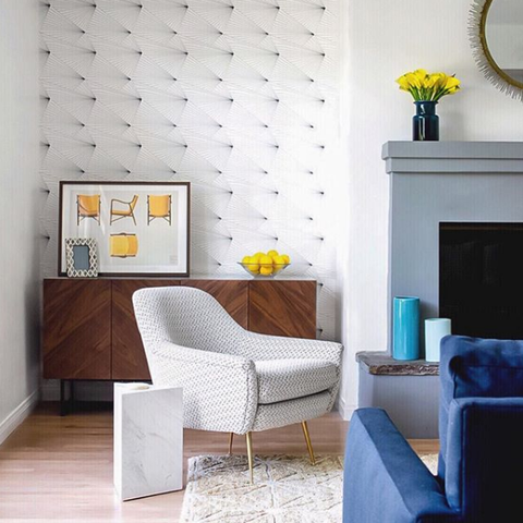 Mid century style living room with monochrome fan wallpaper and yellow accessories.