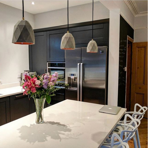 T1 Concrete Pendant Lights by GantLights over a kitchen island.