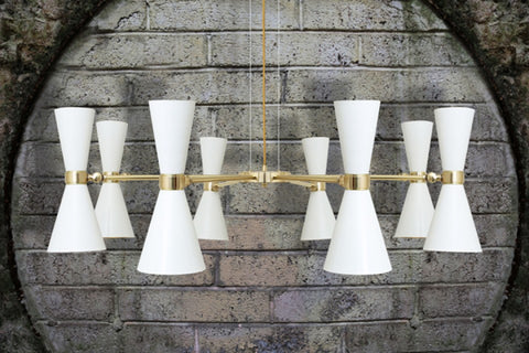 White & gold modern chandelier against a grey brick wall.