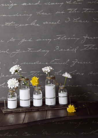 Concrete Loveletter Wallpaper in dark grey with white flower vases displayed.