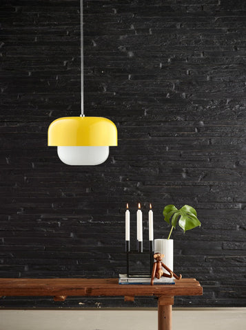 Bold yellow light shown in front of a black brick wall.
