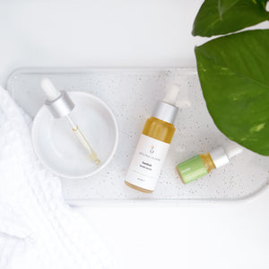 Original Human Co. Facial Serums, Baobab Facial Serum - overhead shot of a full-sized and sample bottle of Original Human Baobab Facial Serum on a white desk.