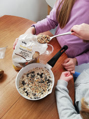 Adding seeds to the suet in the pan