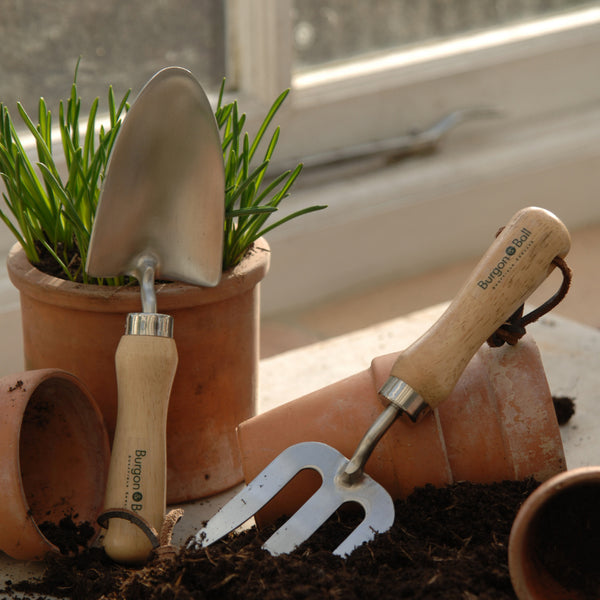 Burgon & Ball children's hand trowel and fork on a table with pots and soil