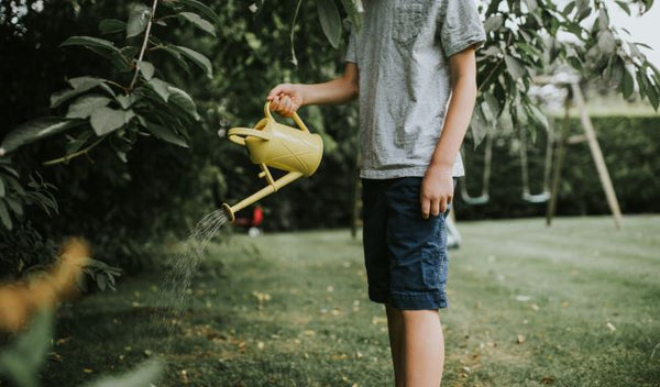 Child using the Haws Bartley Burbler children watering can in yellow