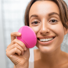 woman holding pink facial cleansing tool
