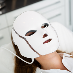 woman laying down wearing an LED face mask