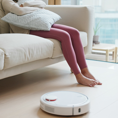 woman sitting on couch near robot vacuum on the floor