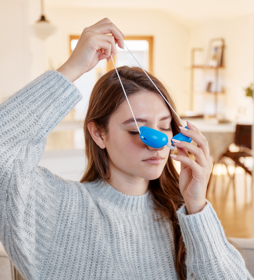 woman placing blue eye mask over her head