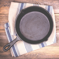 cast iron pan sitting on top of a striped hand towel