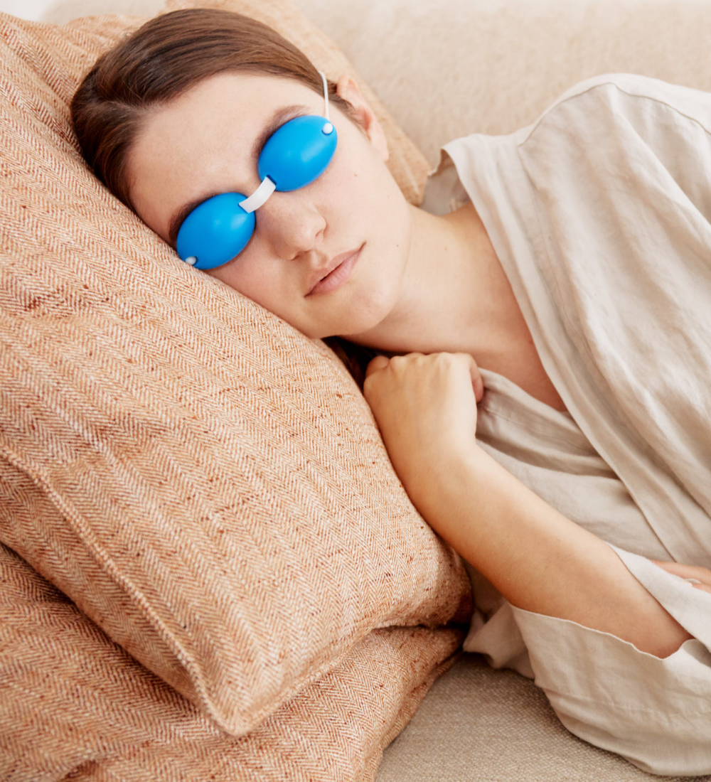 woman laying down on the couch wearing a blue silicone EyeChill eye mask