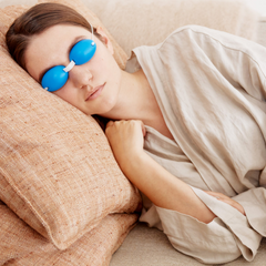 women laying on couch with blue EyeChill eyemask