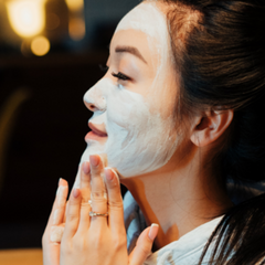 woman applying clay face mask in mirror