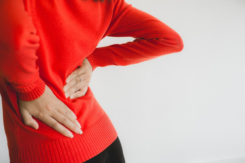back pain for woman in red sweater