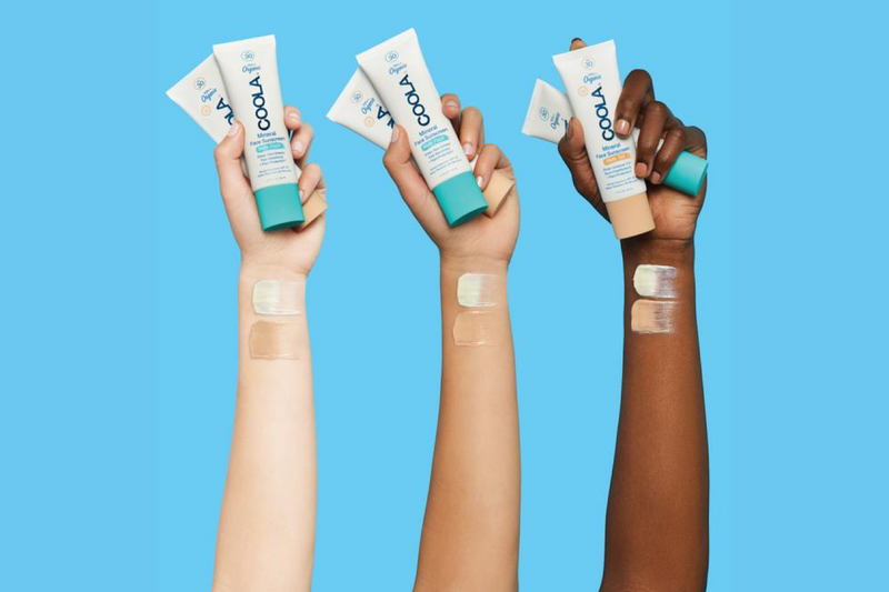 Different skin tone hands holding Coola Suncare Mineral Face Organic Matte Tint Sunscreen Lotion Spf 30